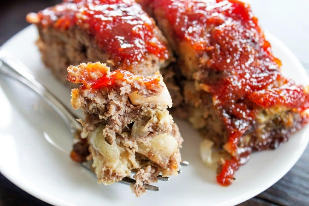BROWN SUGAR MEATLOAF - white plate, metal fork, wooden table