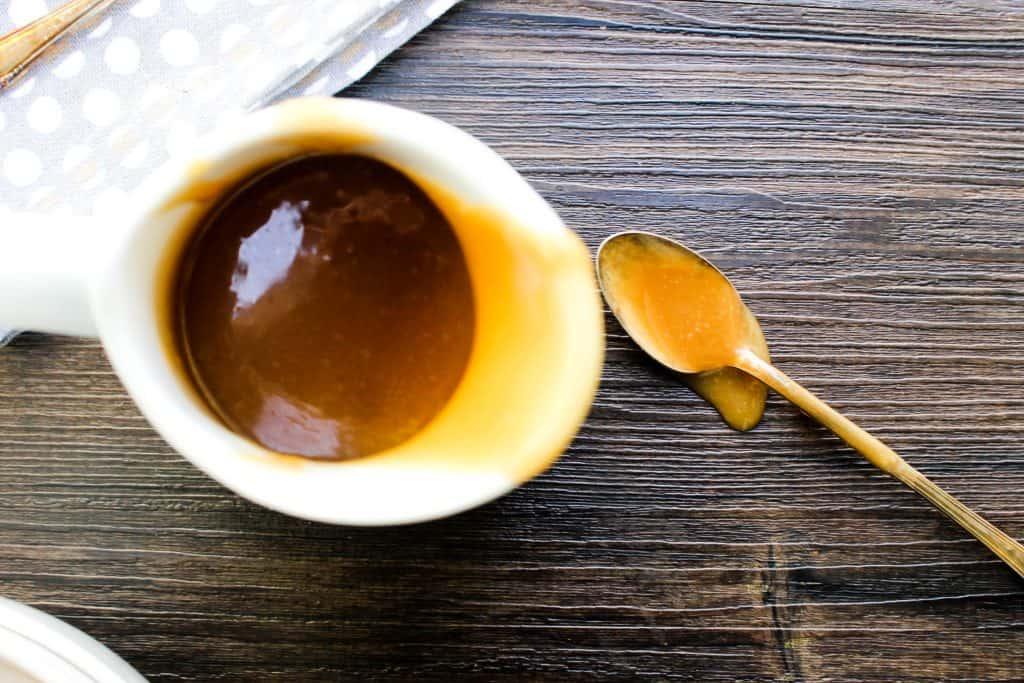 white bowl, caramel sauce, peanut butter, pitcher, white gravy bowl, napkin, spoon