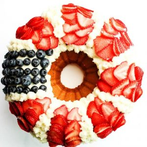Red, White, & Blue Bundt Cake with Fresh Berries is a festive recipe with yellow cake topped with vanilla buttercream and fresh strawberries & blueberries.
