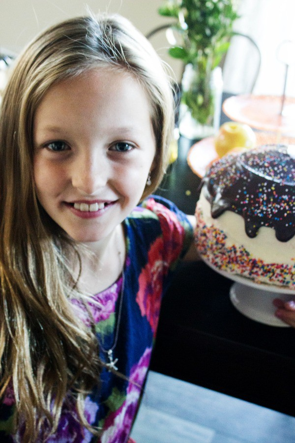 Banana Split Cake is a rich banana cake layered with chocolate, pineapple, and strawberry buttercream that is topped with ganache, cherries, and sprinkles. banana-split-cake-jojo