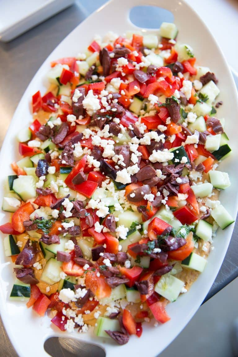 5 Layer Greek Dip - hummus dip, red bell peppers, cucumbers, kalamata olives, feta cheese, parsley and an olive oil drizzle