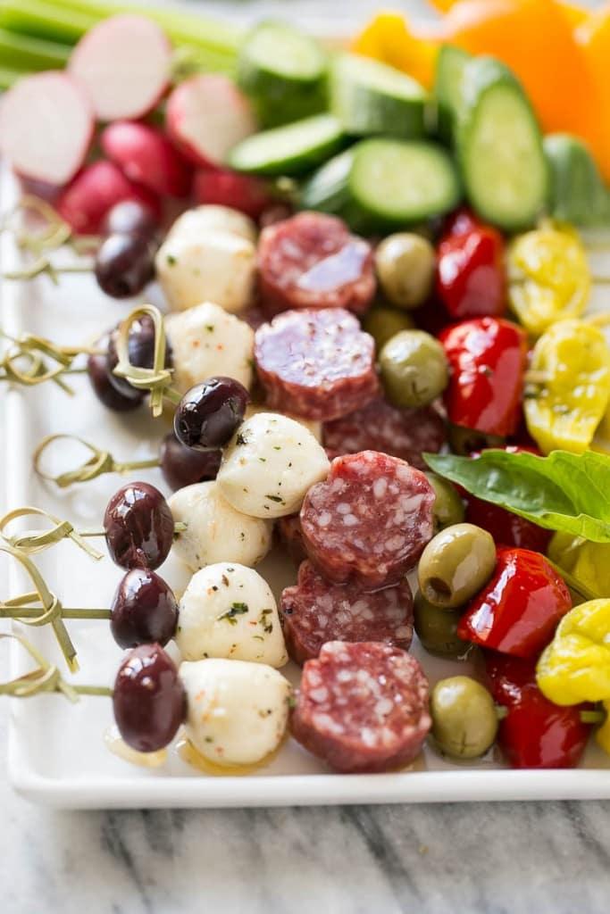 antipasto skewers appetizers - kalamata olives, fresh mozzarella balls, artisan salami, green olives, cherry peppers and pepperoncini