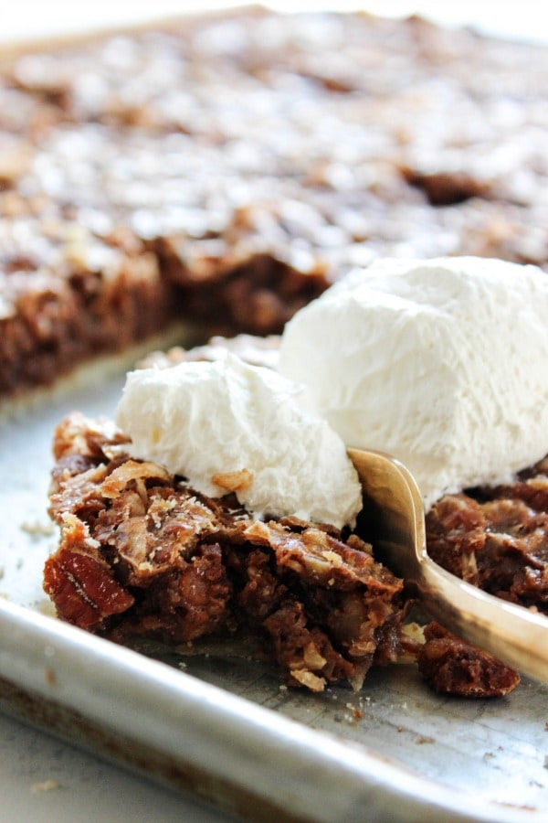 This German Chocolate Slab Pie is the best way to feed a crowd. It's a twist on one of my favorites, with a delicious chocolate, coconut, and pecan filling. german-chocolate-slab-pie-whipped-cream