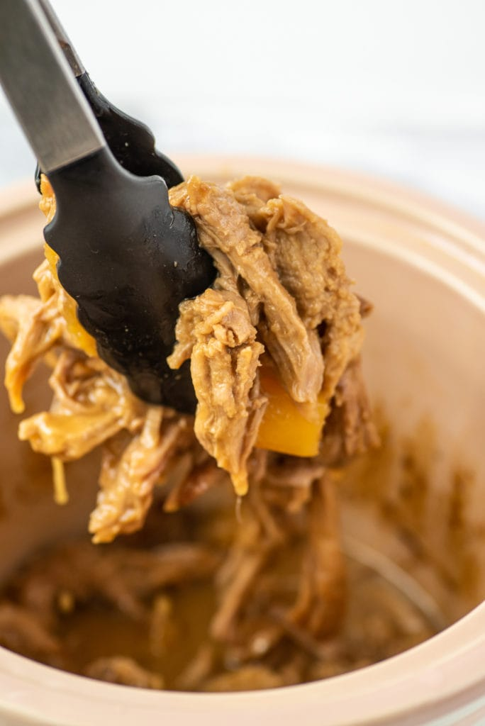 close-up photo of tongs holding shredded pork