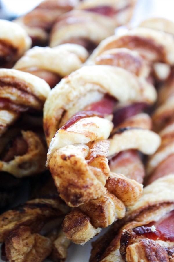 "Crispy Bacon Cinnamon Roll Twists - a delicious ""twist"" on your favorite morning treats. Add in Cream Cheese Frosting, and bring it to a whole new level. Stack of baked twists on white plate"