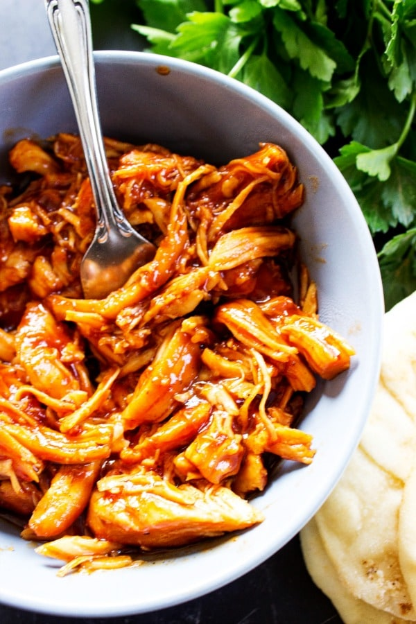 Slow Cooker Chipotle Barbecue Chicken has quickly become our family's favorite barbecue chicken. With the traditional smoky heat from the chipotle seasoning and the sweetness from the barbecue sauce, this creates a mouthwatering combination.- Grey bowl, metal fork, wooden table, herbs