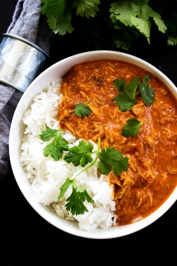 HEALTHY SLOW COOKER CHICKEN TIKKA MASALA a flavorful, lightened up version of this classic Indian dish. With aromatic Indian spices, chicken, tomato sauce and coconut milk, it has become one of my favorite slow cooker meals.- White bowl, black table, grey napkin, metal napkin holder
