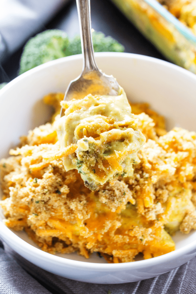 BROCCOLI CHICKEN CURRY CASSEROLE a creamy delicious curry dish made with fresh broccoli chicken and a crispy cheese topping.- White bowl, metal spoon on wooden table
