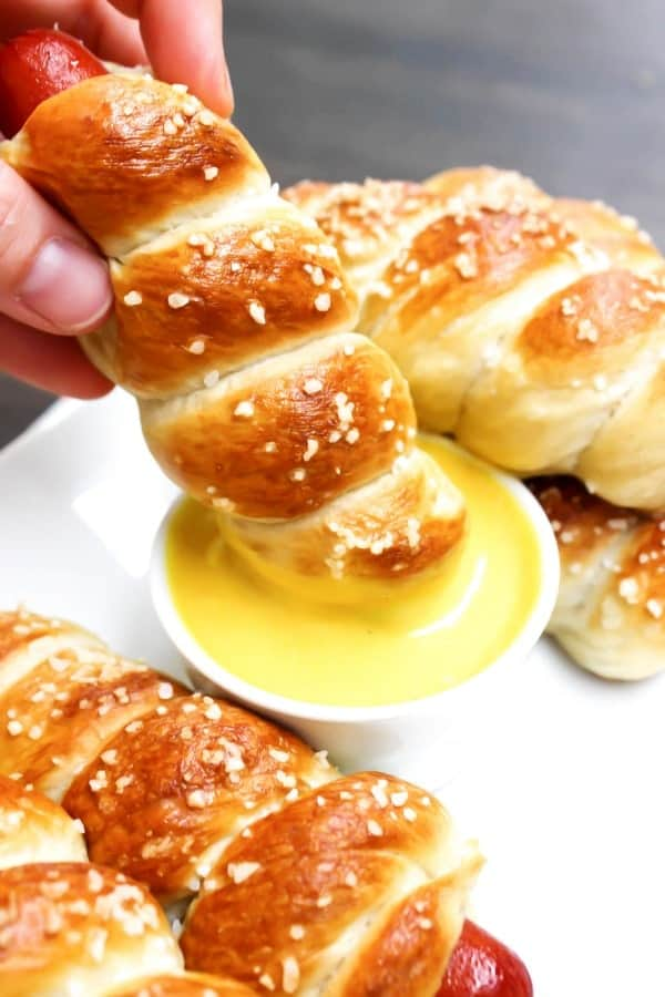 EASY PRETZEL HOT DOGS topped with kosher salt and dipped in honey mustard sauce on white plate