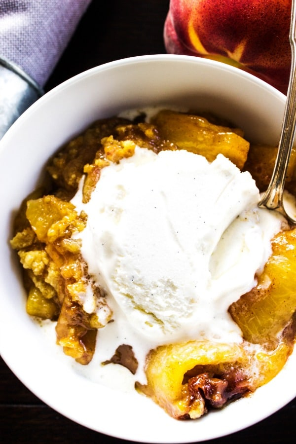 BEST EVER PEACH COBBLER RECIPE. White bowl, grey napkin, peaches, metal spoon