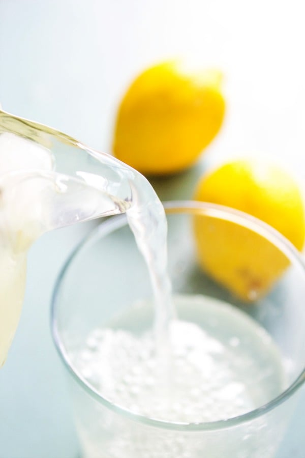 BEST EVER LEMONADE – Glass cup on blue table with lemons