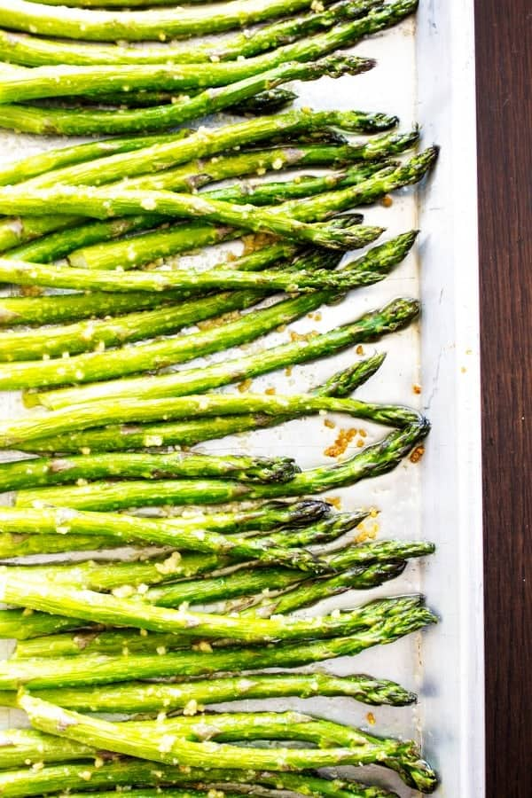 EASY OVEN ROASTED GARLIC ASPARAGUS - Asparagus on white pan