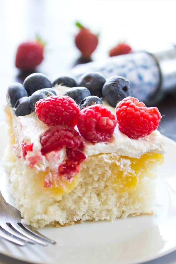 This LEMON BERRY POKE CAKE Cake on white plate, metal fork, strawberries, blue napkin