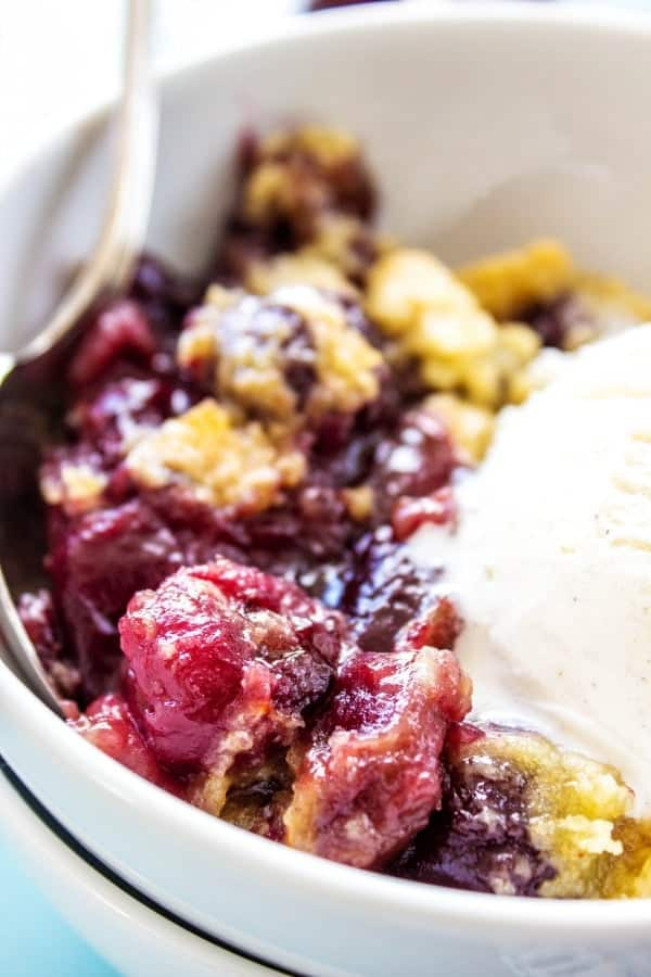 This CHERRY COBBLER RECIPE Dish in white bowl with metal spoon