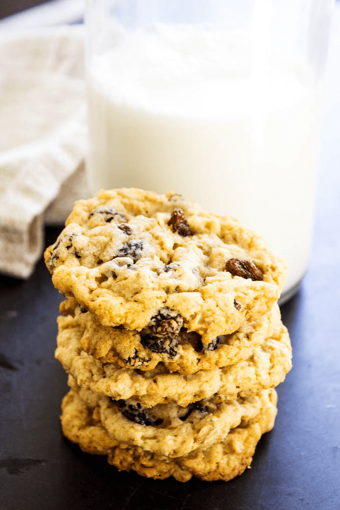 stack of oatmeal raisin cookies with glass of milk