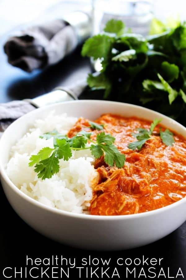 HEALTHY SLOW COOKER CHICKEN TIKKA MASALA a flavorful, lightened up version of this classic Indian dish. With aromatic Indian spices, chicken, tomato sauce and coconut milk, it has become one of my favorite slow cooker meals.- White bowl, herbs, wooden table, grey napkin, metal napkin holder