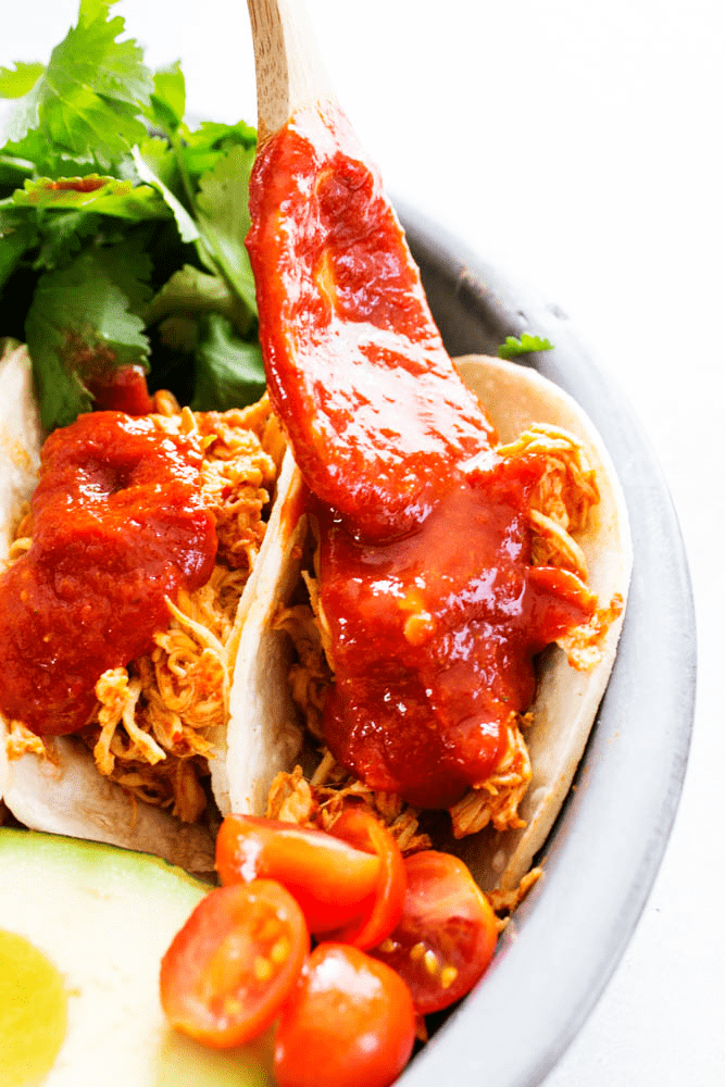 slow cooker chicken, chile colorado sauce, cilantro tacos, tomatoes, avocado, metal plate, spoon