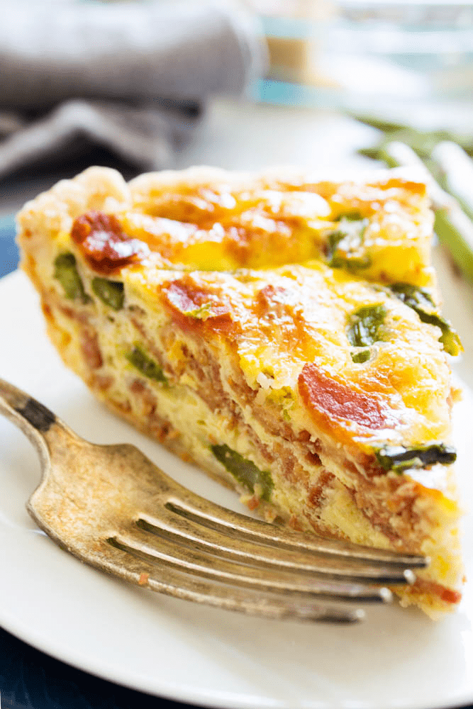 ASPARAGUS BACON QUICHE on white plate with a fork