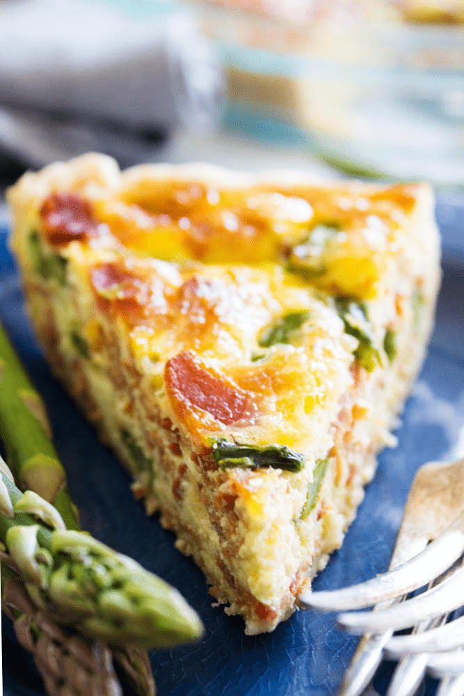 ASPARAGUS BACON QUICHE on blue metal plate with forks and asparagus