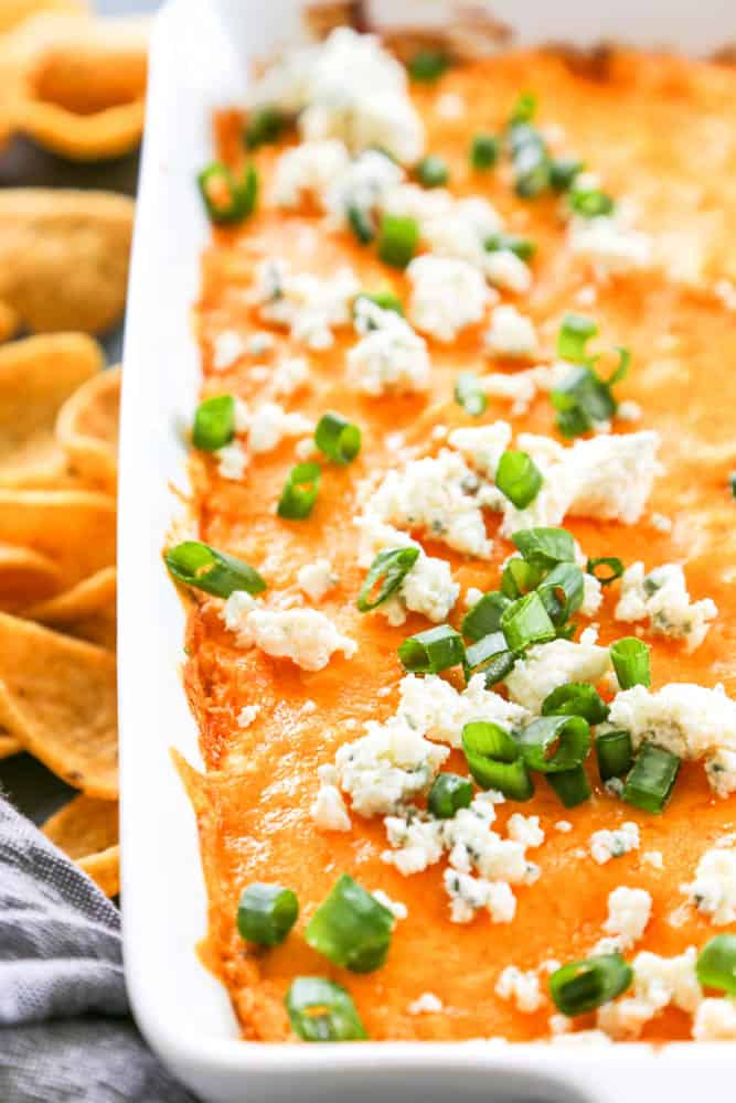 Buffalo Chicken Dip served in white baking dish with Fritos, green onions and blue cheese.