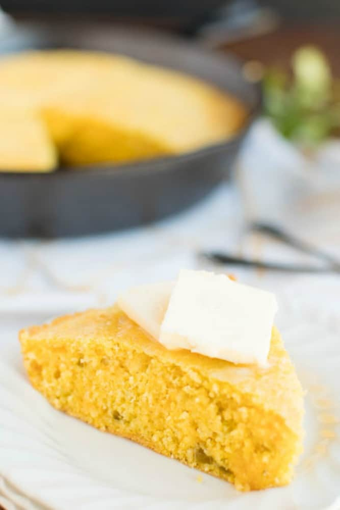 cornbread recipe on a white plate topped with butter