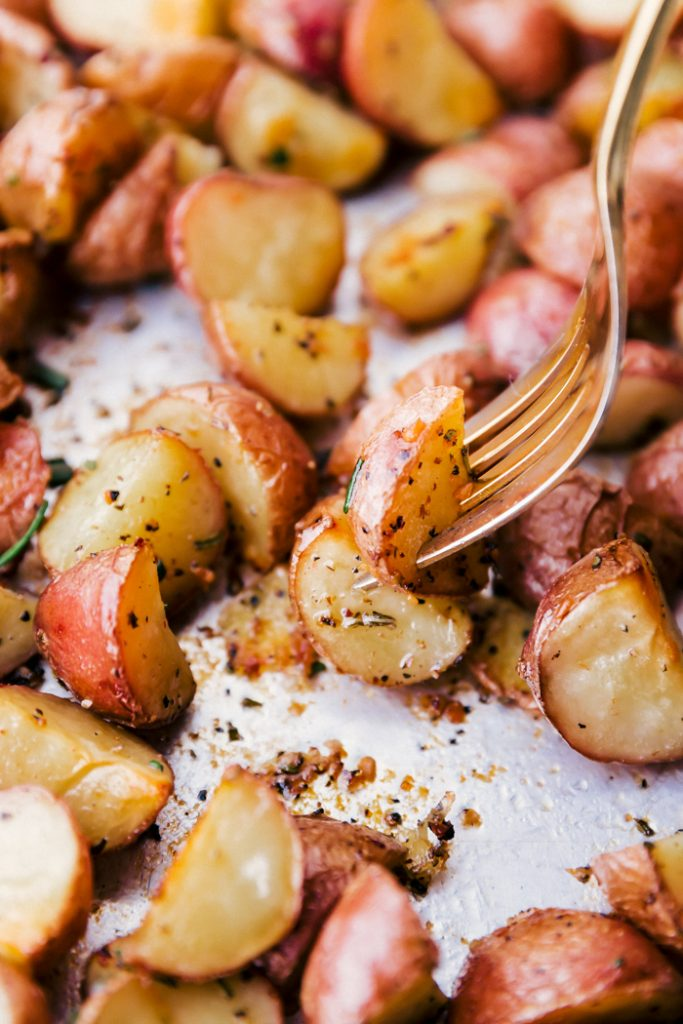 roasted potatoes on a baking sheet with a fork