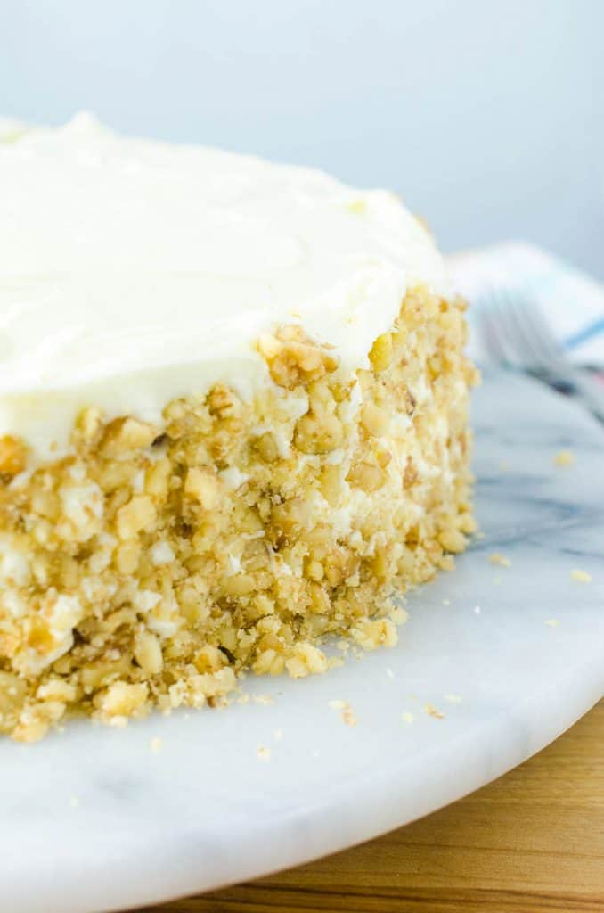 best ever carrot cake with cream cheese frosting and walnuts on cake stand