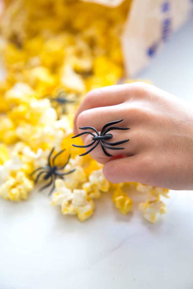 a hand grabbing popcorn with black spider ring on the ring finger