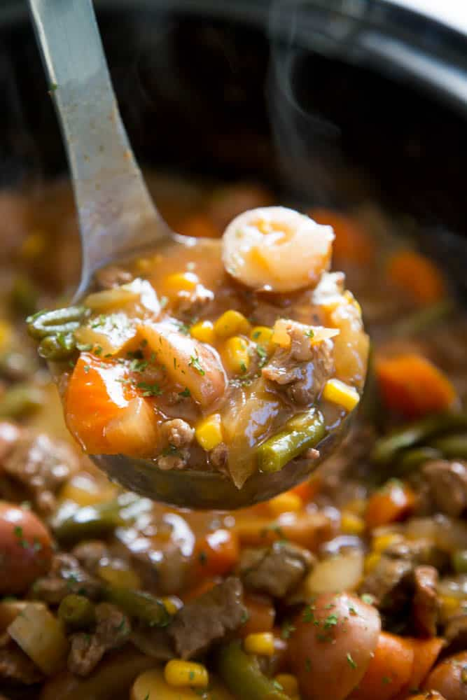 beef stew in slow cooker with ladle